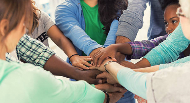 Group of diverse students with hands together